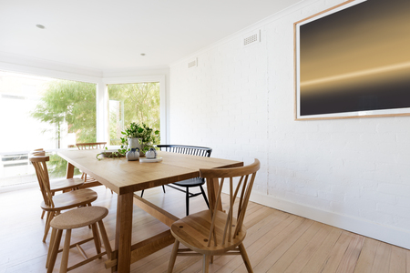 Scandinavian styled white dining room interior with contemporary artwork and pot plant