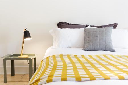 Close-up van luxe bed en nachtkastje met lamp in designer huis Stockfoto