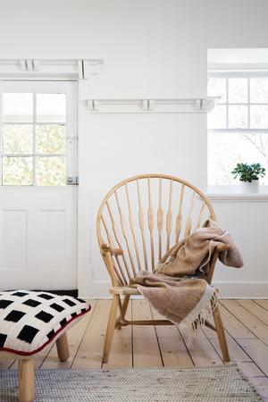 Feature houten arm stoel met gooi en kussen ottoman in modern designer appartement