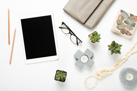 Blank tablet flat lay with desktop objects includng accessories and plants