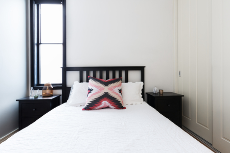 room accent: Modern light bright bedroom with wooden shaker bed and white linen