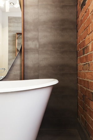en suite: Close up of bath end against grey tiled wall background with text space