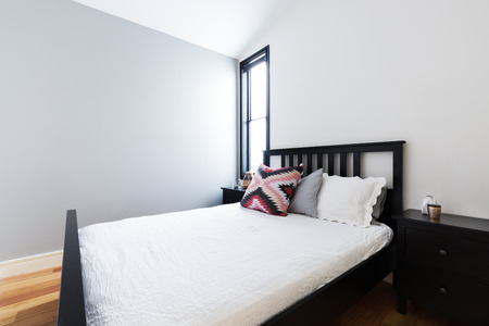 feature wall: Clean crisp modern bedroom with painted light grey feature wall