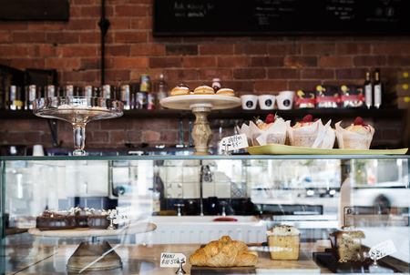 display case: Horizontal cake display case in Melbourne cafe with rustic wall behind