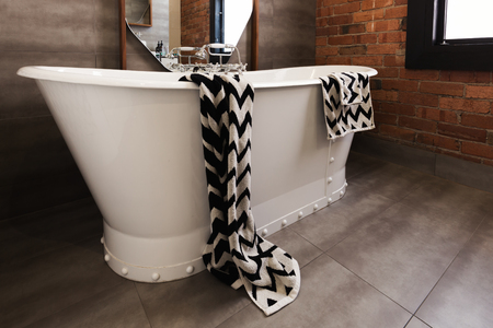 en suite: Styled bath towel draped over a freestanding vintage style bath tub