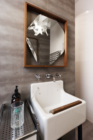 ensuite: White vintage vanity basin with wood detail and mirror against grey tiled wall