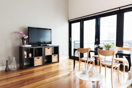 Moderne woonkamer met tv op buffet en tweepersoonsbed naar balkon Stockfoto