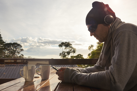 early 40s: Man listening to music on a brisk weekend morning on a balcony with sun behind
