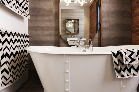 en suite: White free standing vintage style bath tub with chevron pattern balck and white  towels