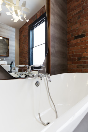 en suite: Looking into large white freestanding vintage bath tub with vintage style tap ware