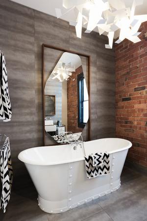ensuite: Freestanding vintage style white bath tub in renovated warehouse apartment