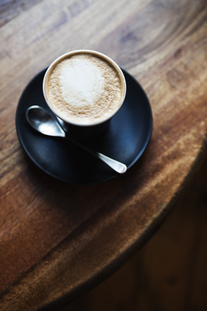 capuchino: Overhead view of cafe latte in black ceramic cup on a wooden restaurant table