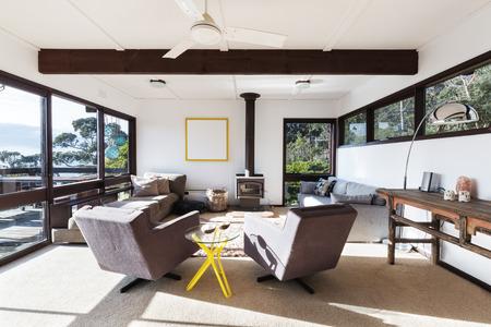 Funky retro beach house woonkamer met jaren '70 stijl fauteuil stoelen en een prachtig uitzicht
