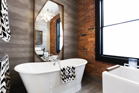 renovated: Horizontal version freestanding vintage style white bath tub in renovated warehouse apartment