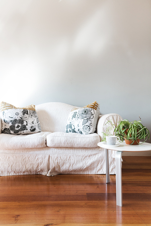 wall decor: Blank painted grey wall with white country style sofa and coffee table