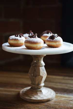 Delicious chocolate topped donuts on a vintage cake stand in a restaurant