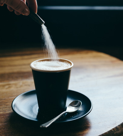 sachet: Action of pouring a sachet of sugar into a cafe latte at a restaurant