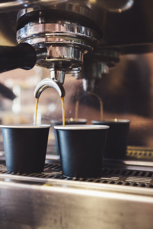 Espresso machine making two coffee in black cups in a cafe