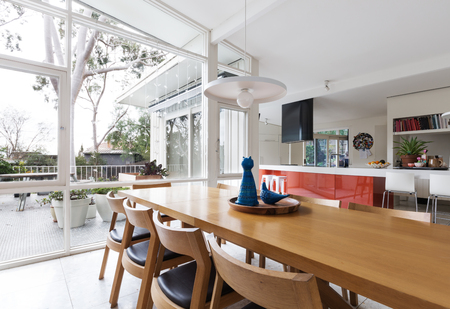 Scandinavian styled dining room and open plan kitchen with patio outlook