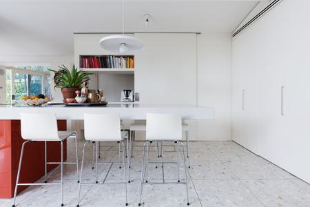 banco blanco quebradizo limpio moderno isla de cocina con sillas altas y suelo de terrazo Foto de archivo