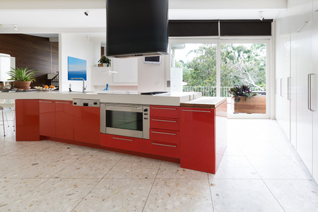 Orange red kitchen cabinets in island bench in modern luxury Australian home Standard-Bild