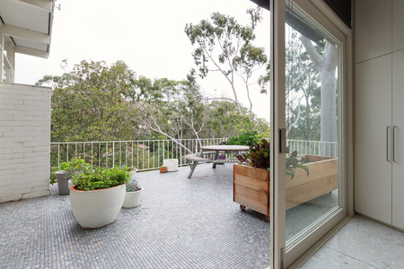 View of treetops from large mosaic tiled terrace in Australian luxury home