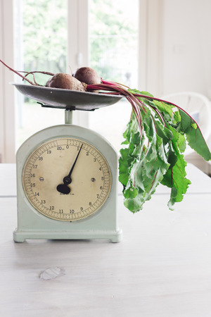 lopsided: Raw beetroot vegetables with leaves on vintage scales in a light bright contemporary home