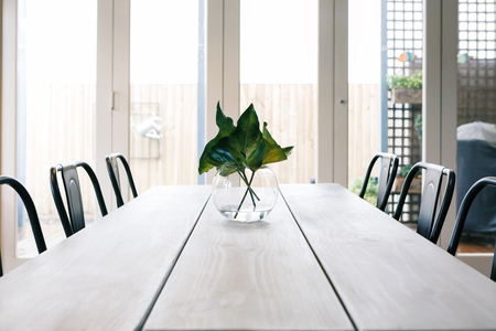 styled interior: Uncluttered light bright contemporary dining room table with glass doors background