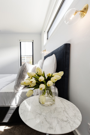 Yellow tulips on a marble bedside table with gold wall light above