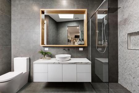 헤링본 샤워 기와가 달린 현대적인 회색 디자이너 욕실