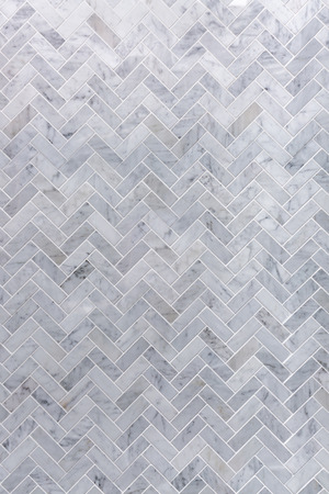 Background of grey and white marble tile in herringbone pattern