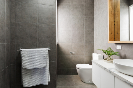 ensuite: Charcoal grey modern bathroom with marble benctop and wood mirror Stock Photo