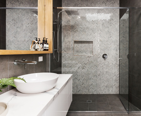 tiled wall: Marble mosaic herringbone tiled shower feature wall in a contemporary ensuite bathroom