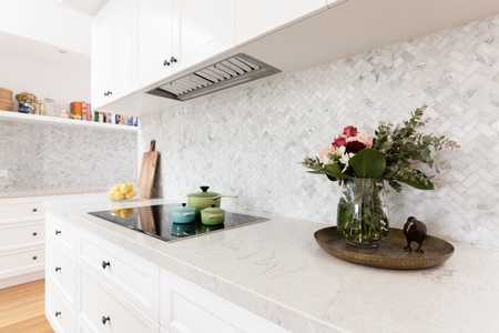 Rear kitchen bench styled with cut flowers and colorful saucepans Фото со стока - 92160604