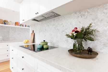 Achterste keukenbank gestyled met snijbloemen en kleurrijke steelpannen