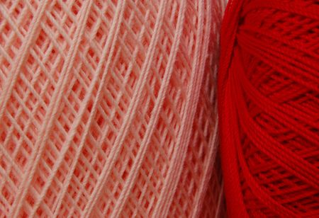 Two spools of cotton crochet thread in red and pink