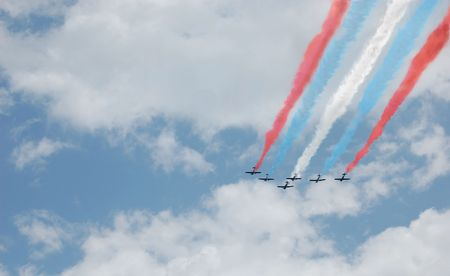 Six planes with red, white, and blue smoke trails flying in formation