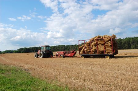 A red tractor pulling a wagon filled with bales of hay
