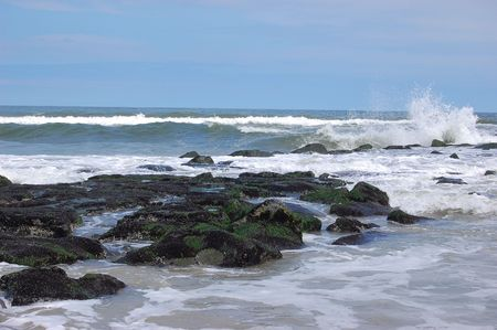 Ocean with a rock jetty and a splashing wave