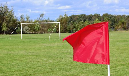 A soccer field with a goal and a red flag Stock Photo