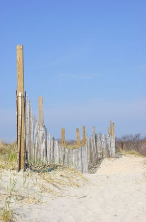 A fenced pathway through the sand dunes
