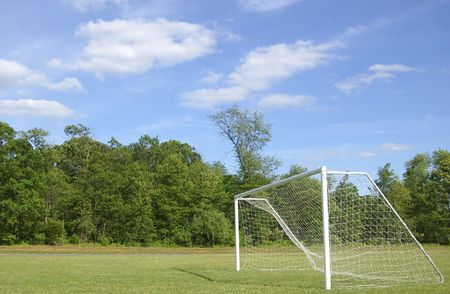 An empty soccer net on a bright day