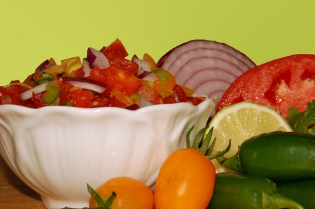 Fresh salsa surrounded by ingredients on a lime green background Stock Photo