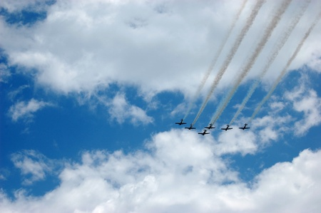 Six planes with smoke trails in a cloudy blue sky
