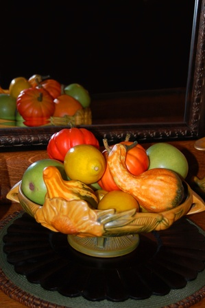 An assortment of colorful fruits an gourds reflected in a mirror