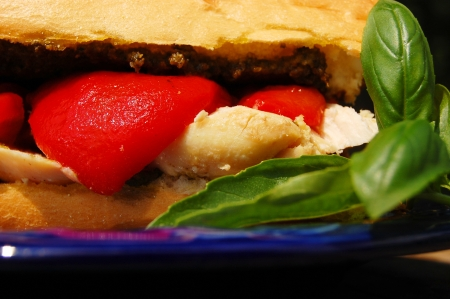 A crusty roll spread with basil pesto and filled with chicken breast and roasted red peppers