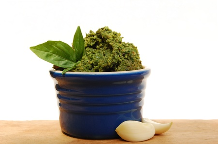 Pesto in a blue ramekin with garlic and basil Stock Photo