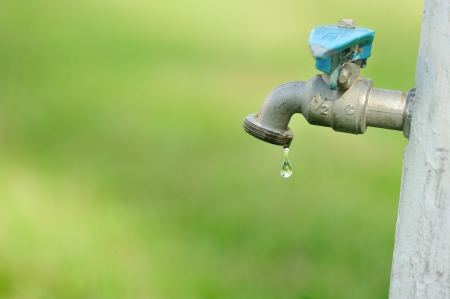 Water drop falling from an old outdoor tap