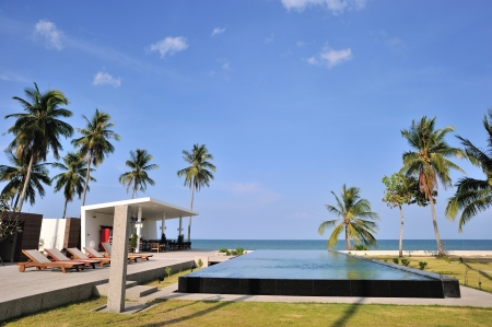A swimming pool near by the beach surrounded by coconut trees