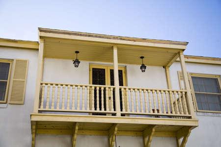 second floor: Yellow and white balcony on second floor, overlooking street Stock Photo